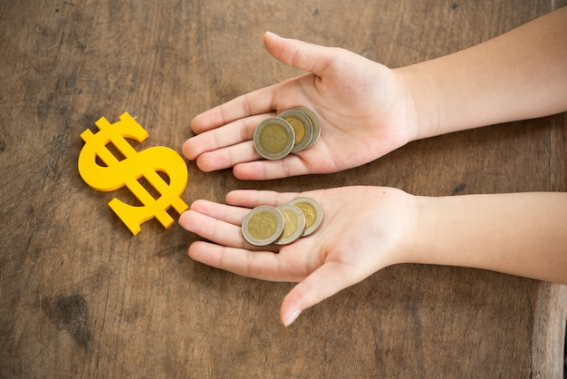 Niño con monedas y signo de dólar amarillo Foto gratis
