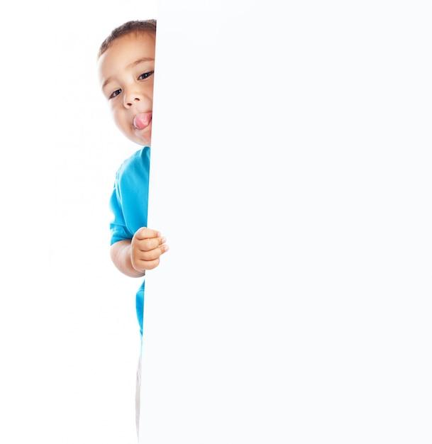 Niño mostrando la lengua y sujetando un cartel en blanco Foto gratis