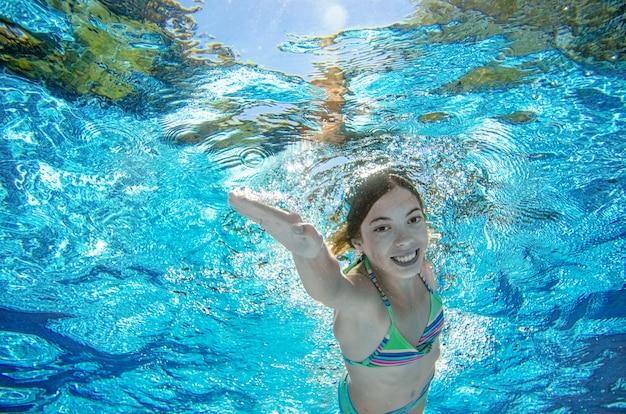 El niño nada bajo el agua en la piscina, la niña adolescente activa y feliz se zambulle y se divierte bajo el agua, se ejercita y practica deporte en vacaciones familiares en el resort Foto Premium