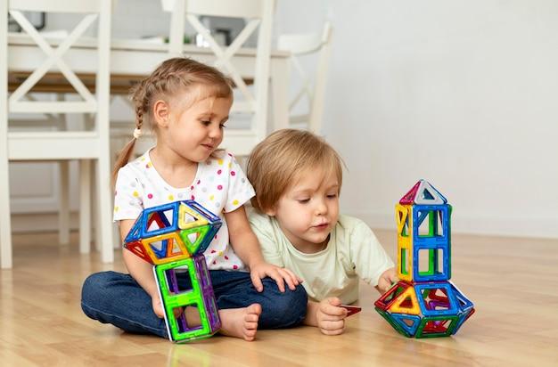 Niño y niña en casa jugando con juguetes juntos Foto gratis