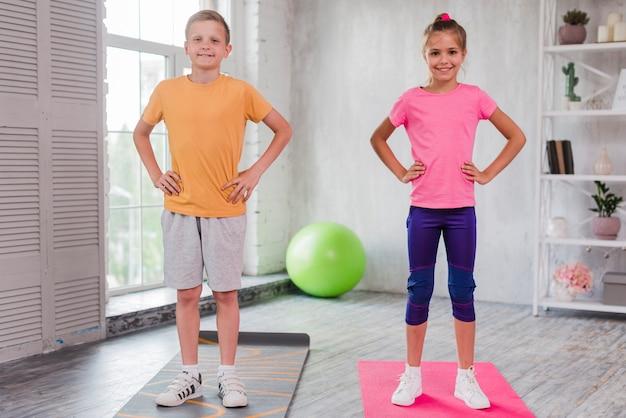 Niño y niña sonrientes que se colocan en la estera del ejercicio con las manos en cadera Foto gratis