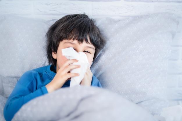Niño niño sonarse la nariz. niño enfermo con una servilleta en la cama. niño alérgico, temporada de gripe. niño con rinitis fría, enfríe Foto Premium