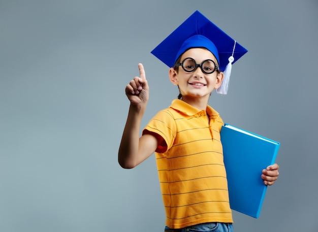 Niño orgulloso con gafas y gorro de graduación Foto gratis