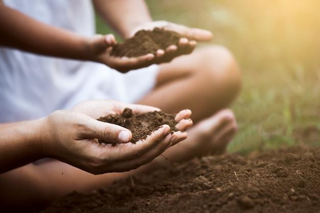 El niño y el padre sostienen el suelo y preparan el suelo para plantar el árbol juntos. Foto Premium