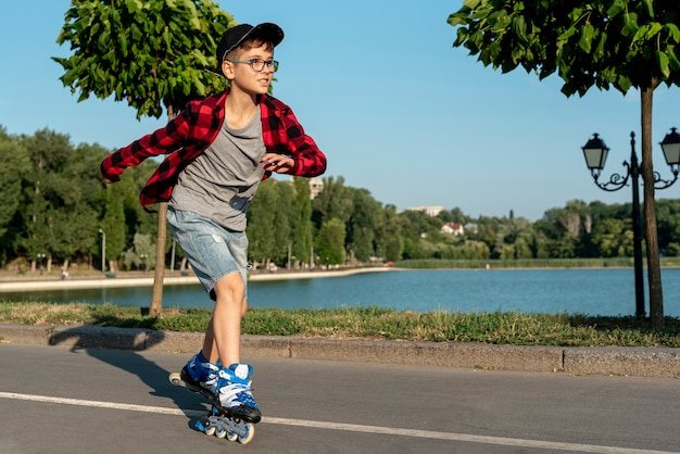 Niño con patines azules en el parque Foto gratis