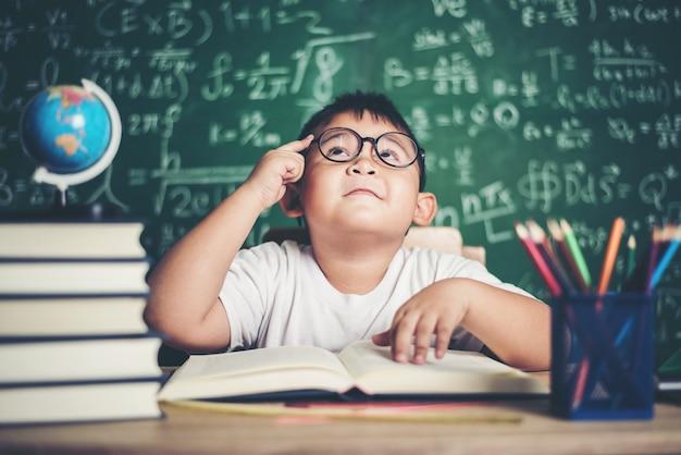 Niño pensativo con el libro en el aula
