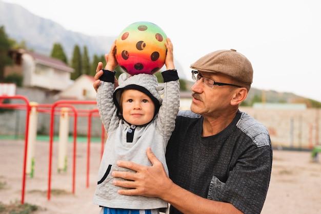 Niño pequeño con el abuelo jugando con pelota Foto gratis