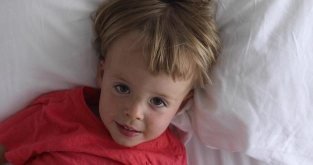 El niño pequeño se acuesta en la cama. el muchacho hermoso miente en la opinión superior del niño feliz y alegre de la ropa en colores pastel blanca Foto Premium