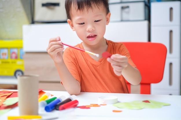Un niño pequeño asiático de 3 años disfruta usando pegamento haciendo artes en casa, papel divertido y manualidades de pegamento para niños pequeños, children's art project Foto Premium