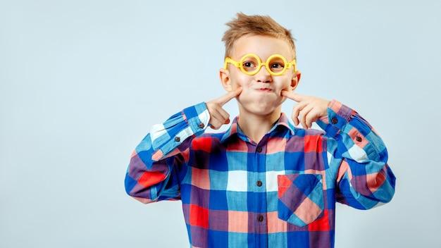 Niño pequeño con camisa a cuadros de colores, gafas de plástico divirtiéndose en el estudio Foto Premium