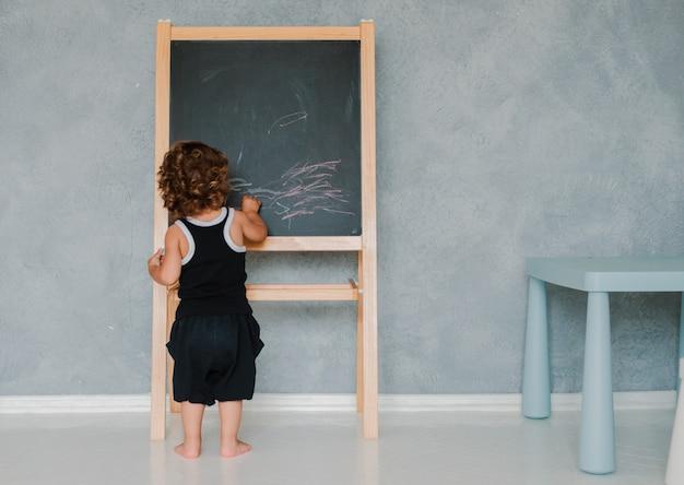 Niño pequeño dibuja con tiza sobre una pizarra negra tablero en casa en la guardería contra una pared gris. Foto Premium