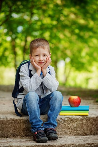 Niño pequeño divertido que se sienta en piedra con los libros, la manzana y la mochila en fondo verde de la naturaleza. volver al concepto de escuela. Foto Premium