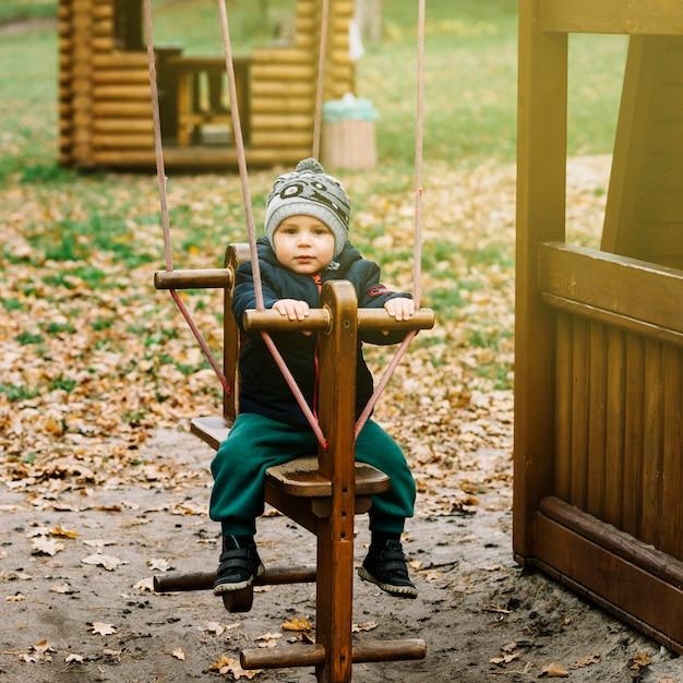 Niño pequeño en columpio en jardín de otoño | Descargar Fotos gratis