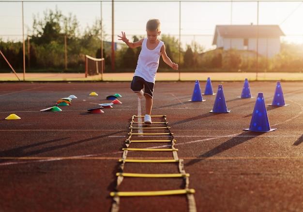 Niño pequeño en el entrenamiento de verano temprano en la mañana saltando sobre trammels en el campo de entrenamiento. Foto Premium