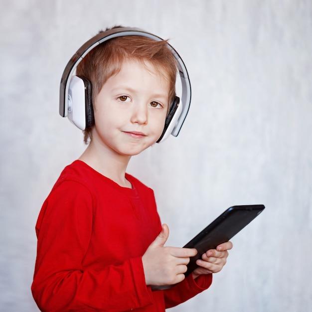 Niño pequeño escuchando música o mirando películas con auriculares y usando una tableta digital, jugando. Foto Premium
