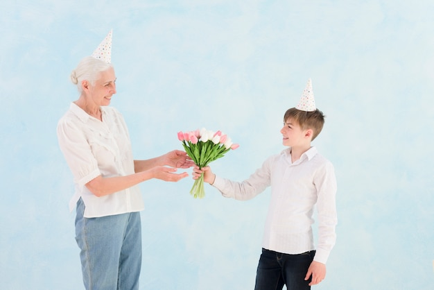 El niño pequeño feliz que da el tulipán florece el ramo a su abuela contra el contexto azul Foto gratis