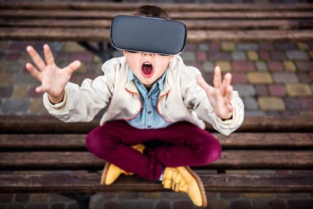 Niño pequeño en gafas de realidad virtual en el parque Foto Premium