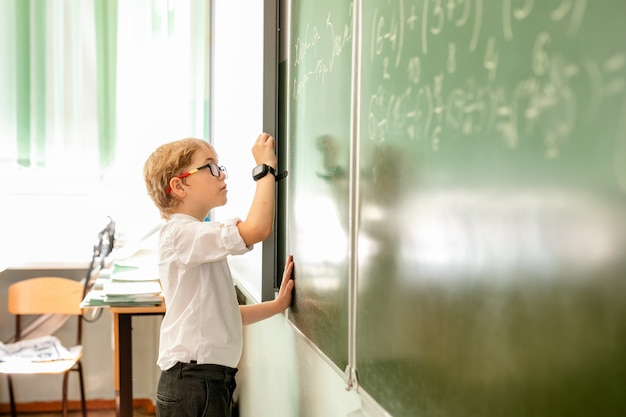 Niño pequeño con grandes gafas negras y camisa blanca de pie cerca de la pizarra de la escuela con un trozo de tiza haciendo cara de pensamiento inteligente Foto Premium