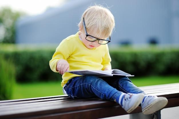 Niño pequeño lindo que lee un libro al aire libre en día de verano caliente. concepto de regreso a la escuela Foto Premium