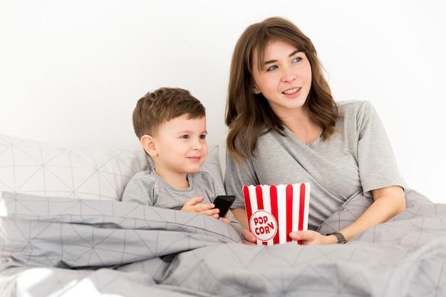 Niño pequeño con mamá en la cama Foto gratis