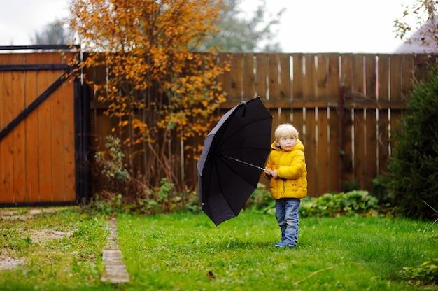 Niño pequeño que camina en el tiempo nublado lluvioso del otoño. niño con gran paraguas negro bajo la lluvia. actividad al aire libre de otoño Foto Premium