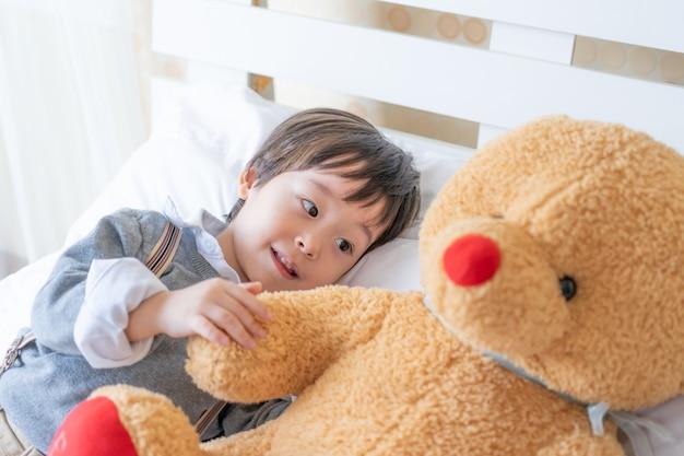 Niño pequeño que juega con el oso de peluche grande en cama Foto gratis