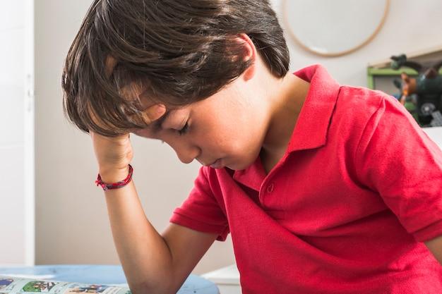 Niño pequeño que pone la mano en la cabeza Foto gratis