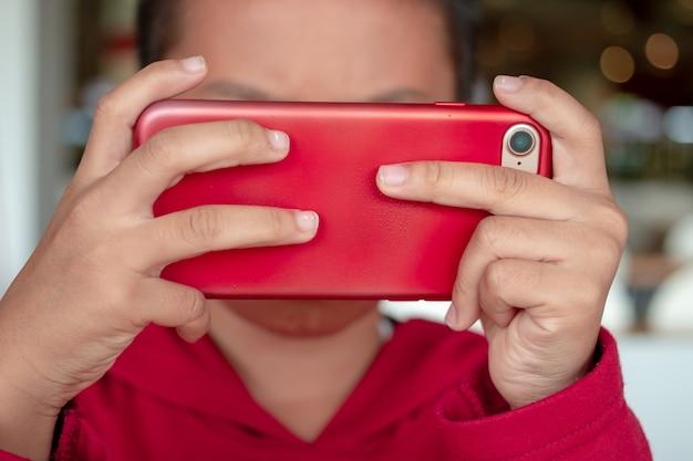 Niño pequeño que sostiene smartphone en posición horizontal. juego para niños, navegando en línea, aprendiendo. Foto Premium