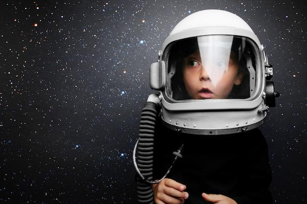 Un niño pequeño quiere volar un avión con un casco de avión Foto Premium