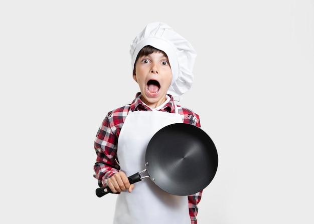 Niño pequeño con una sartén sorprendido Foto gratis