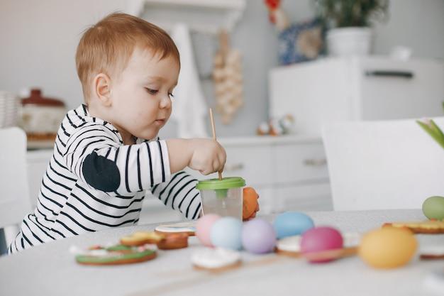 Niño pequeño sentado en una pintura de cocina Foto gratis