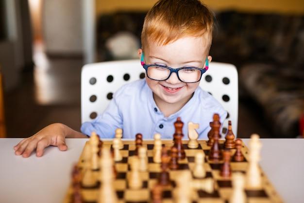 Niño pequeño con síndrome de down con grandes gafas azules jugando al ajedrez en el jardín de infantes Foto Premium