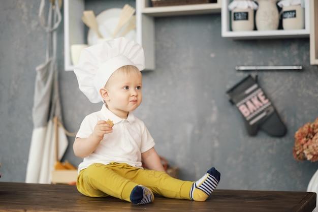 Un niño pequeño con sombrero de chef en la cocina sentado en la mesa y comer Foto Premium