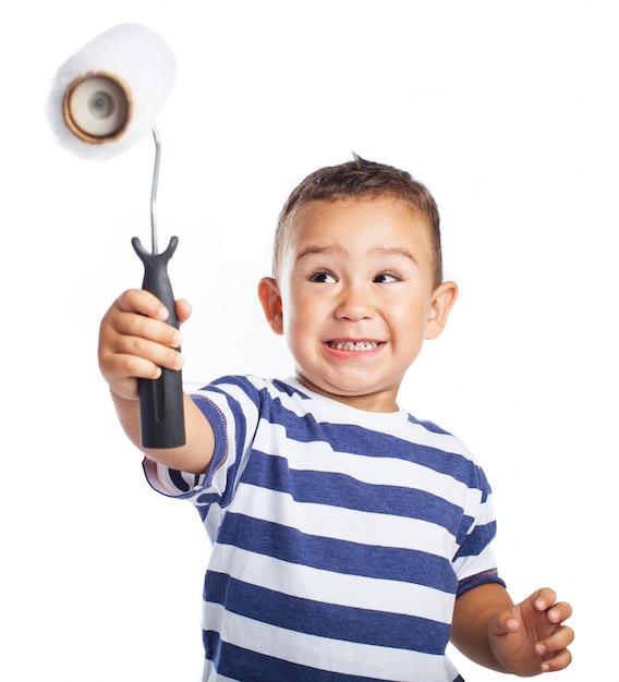 Ni o peque o sonriendo y sujetando en alto un rodillo de - Foto nino pequeno ...