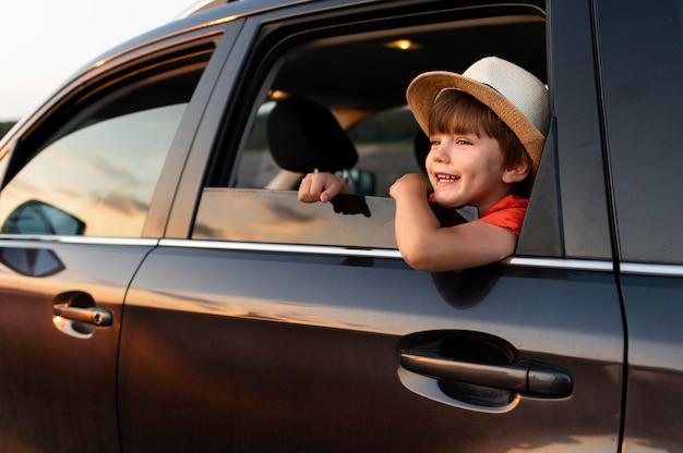Niño pequeño sonriente en coche Foto gratis