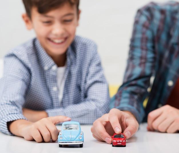 Niño pequeño sonriente que juega con los coches de juguete Foto gratis