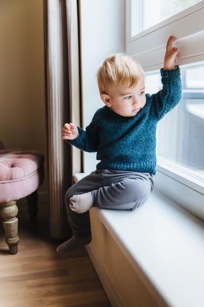 Niño pequeño travieso con cabello rubio y ojos azules, se sienta en el alféizar de la ventana, mira por la ventana Foto Premium