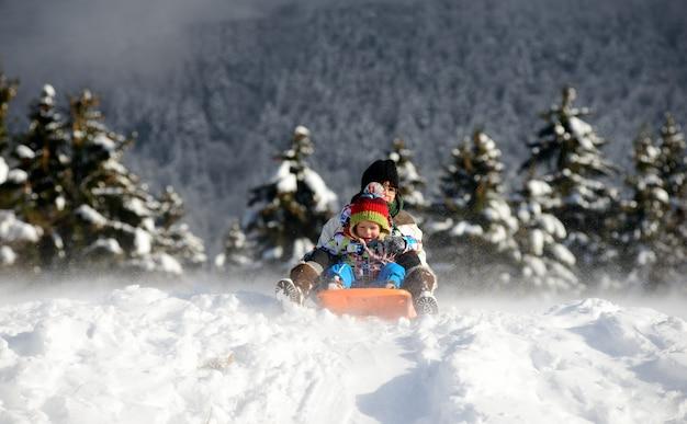 Un niño pequeño en trineo en la nieve. Foto Premium