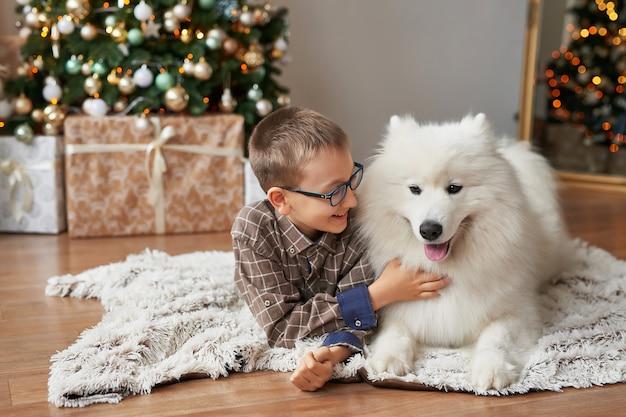 Niño con perro cerca del árbol de navidad en navidad Foto Premium