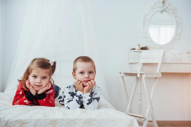 Niño en pijama suave y cálido jugando en la cama Foto Premium