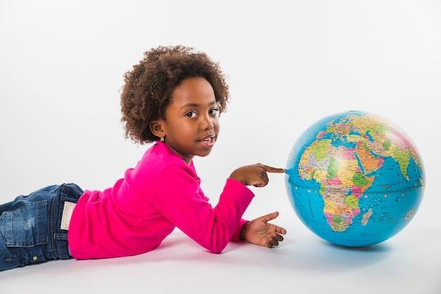 Niño poniendo y con globo en estudio Foto gratis