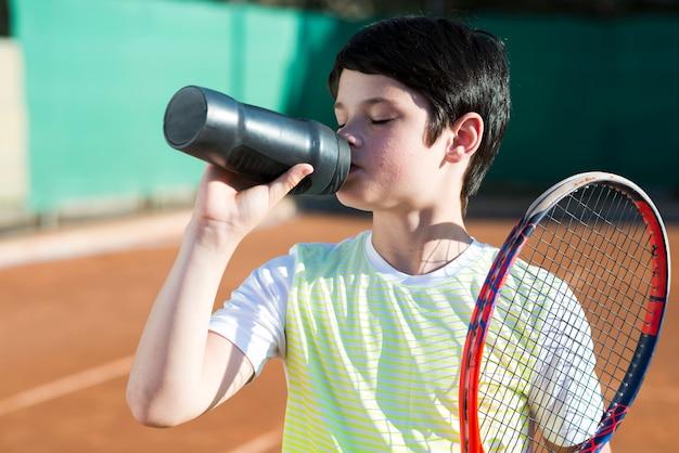 Niño con raqueta en el hombro y agua potable. Foto gratis