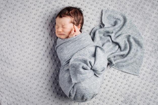 Niño recién nacido en el cocon acostado sobre una manta gris. Foto Premium