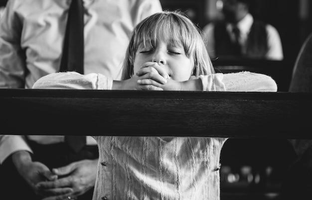 Un niño rezando dentro de la iglesia. Foto gratis