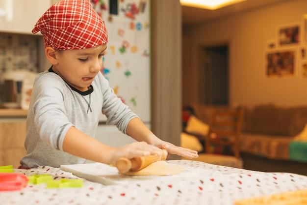 Niño con un rodillo para hornear galletas de navidad Foto Premium