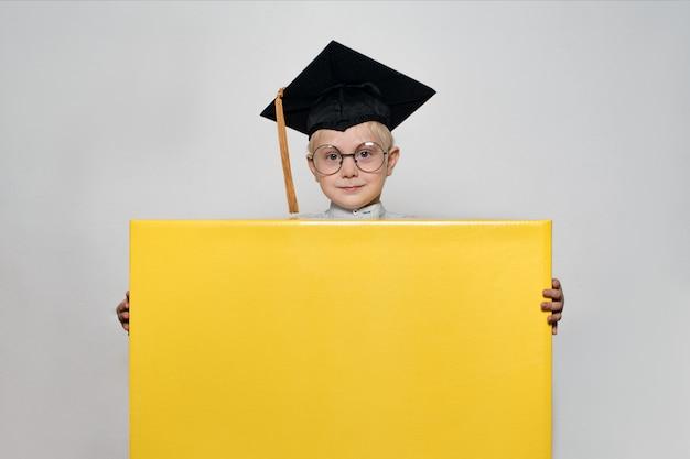 Niño rubio con un sombrero académico y gafas tiene una gran caja. fondo blanco. concepto de escuela Foto Premium