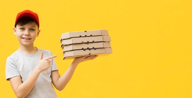 Niño señalando cajas de pizza Foto gratis