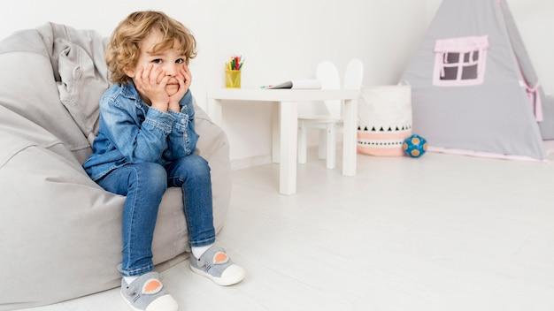 Niño sentado en el sofá en casa Foto gratis