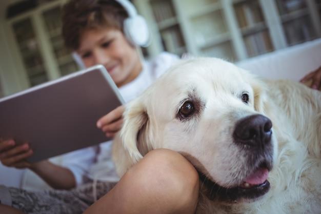 Niño sentado en el sofá con una mascota y escuchando música en tableta digital Foto Premium