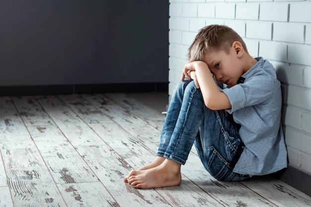 Un niño se sienta solo con una sensación triste en la escuela cerca de la pared Foto Premium